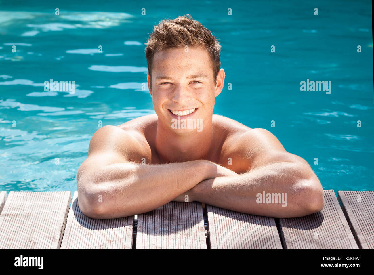 junger dunkelblonder Mann am Beckenrand eines Swimmingpools, Deutschland | young blond man in a swimming pool, Germany | BLWS486392.jpg [ (c) blickwin - Stock Image