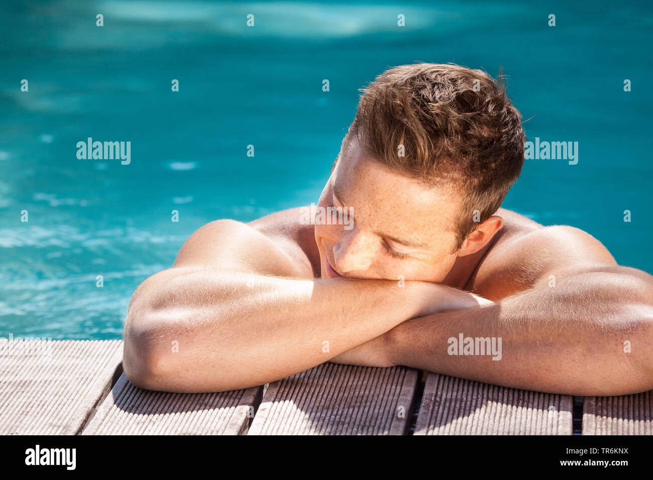 junger dunkelblonder Mann am Beckenrand eines Swimmingpools, Deutschland | young blond man in a swimming pool, Germany | BLWS486394.jpg [ (c) blickwin - Stock Image