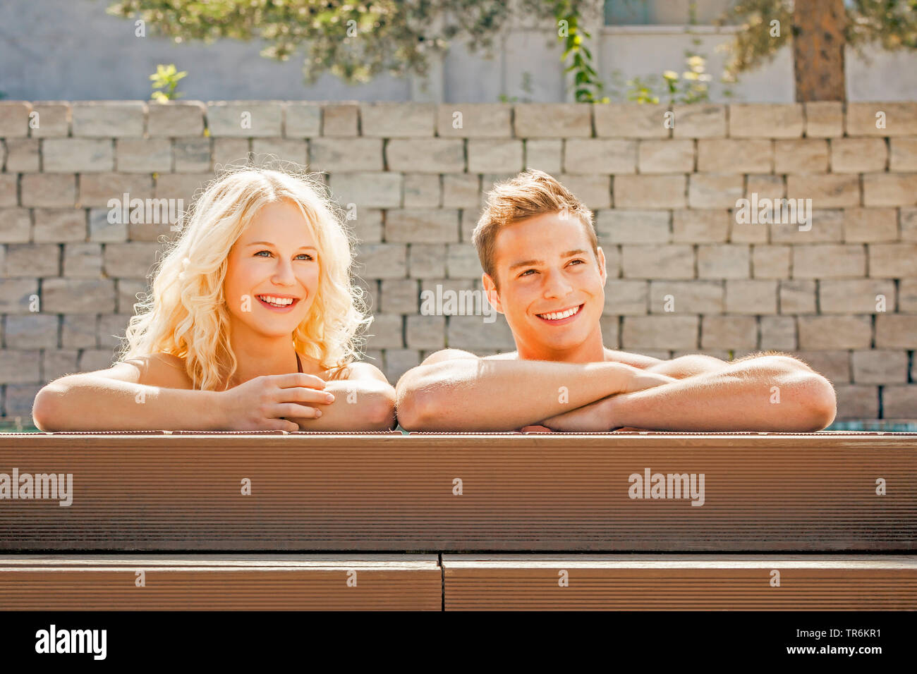 junges Paar entspannt sich am Schwimmbeckenrand, Deutschland | young couple relaxing at a pool, Germany | BLWS486422.jpg [ (c) blickwinkel/McPHOTO/M. - Stock Image