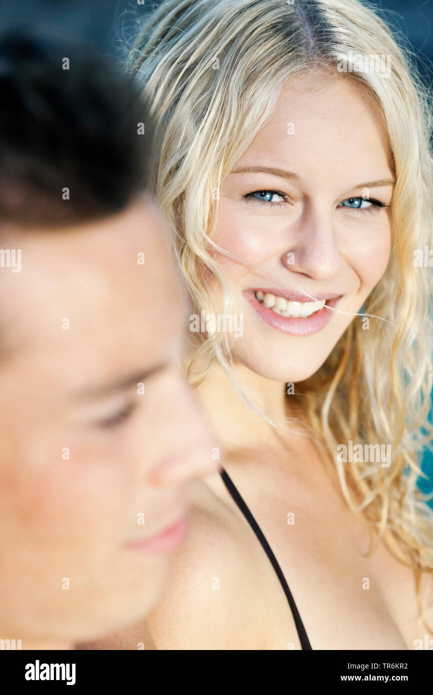 junges Paar am Schwimmbeckenrand, sie schaut ihn gluecklich an, Deutschland | young couple relaxing at a pool, Germany | BLWS486427.jpg [ (c) blickwin - Stock Image