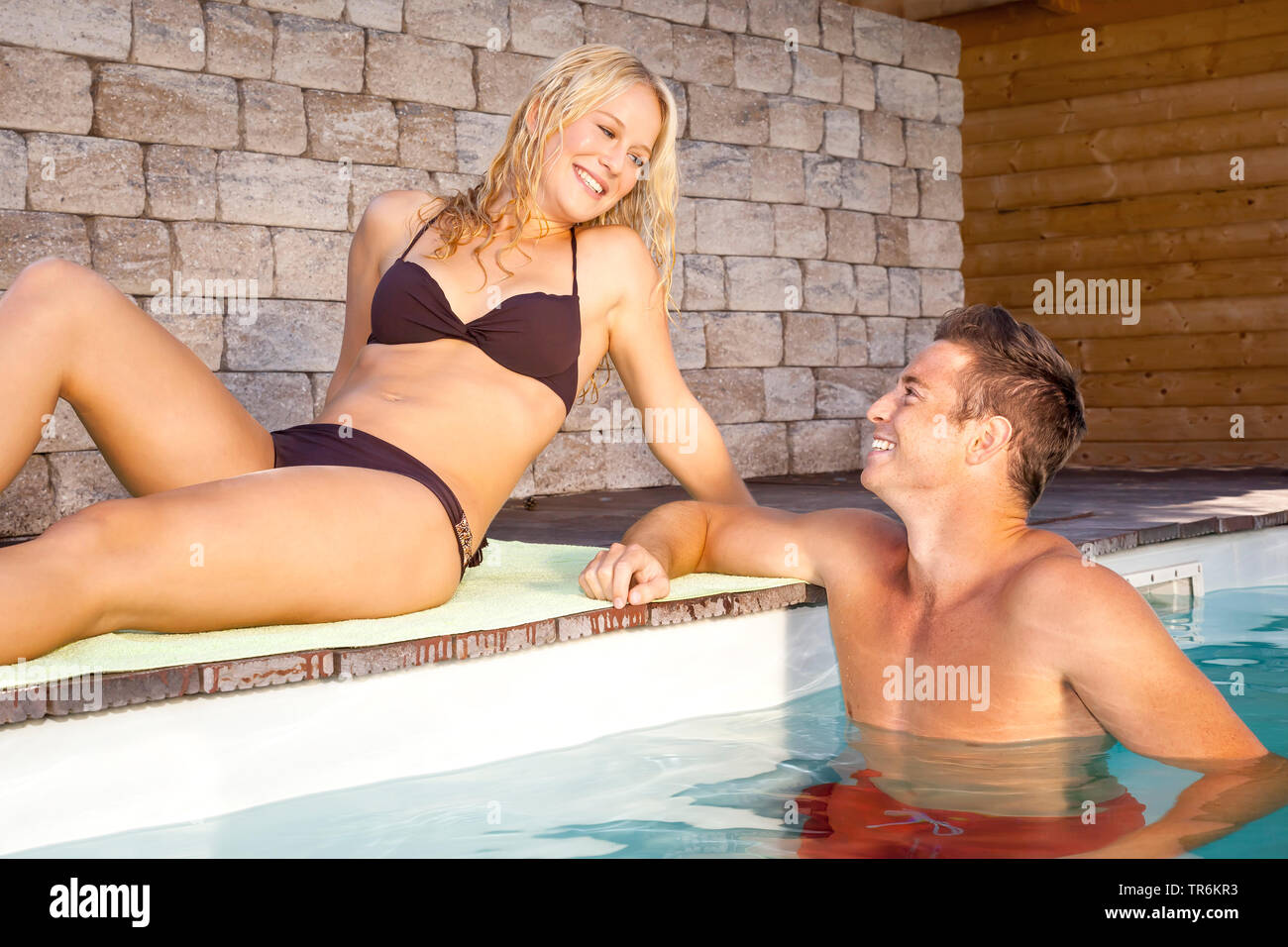 junges Paar entspannt sich am Schwimmbeckenrand, Deutschland | young couple relaxing at a pool, Germany | BLWS486428.jpg [ (c) blickwinkel/McPHOTO/M. - Stock Image