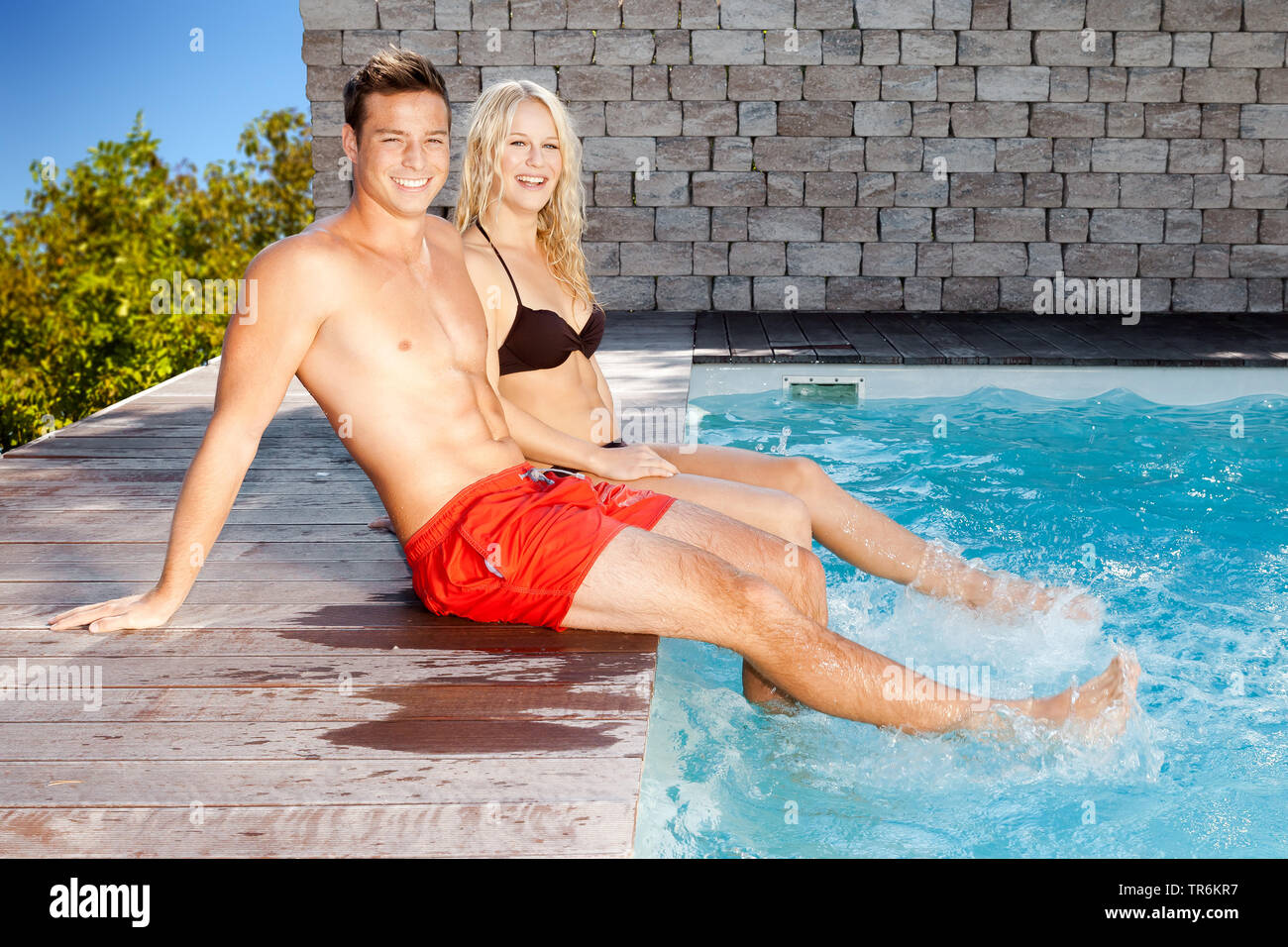 junges Paar entspannt sich am Schwimmbeckenrand, Deutschland | young couple relaxing at a pool, Germany | BLWS486431.jpg [ (c) blickwinkel/McPHOTO/M. - Stock Image