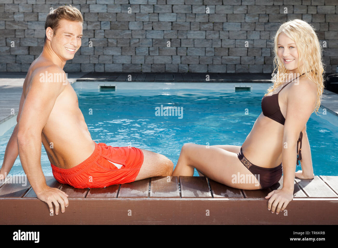 junges Paar entspannt sich am Schwimmbeckenrand, Deutschland | young couple relaxing at a pool, Germany | BLWS486436.jpg [ (c) blickwinkel/McPHOTO/M. - Stock Image