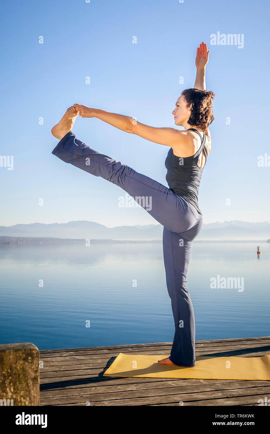 woman doing yoga exercises at a lake, Utthita Hasta Padangusthasana, Germany, Bavaria - Stock Image