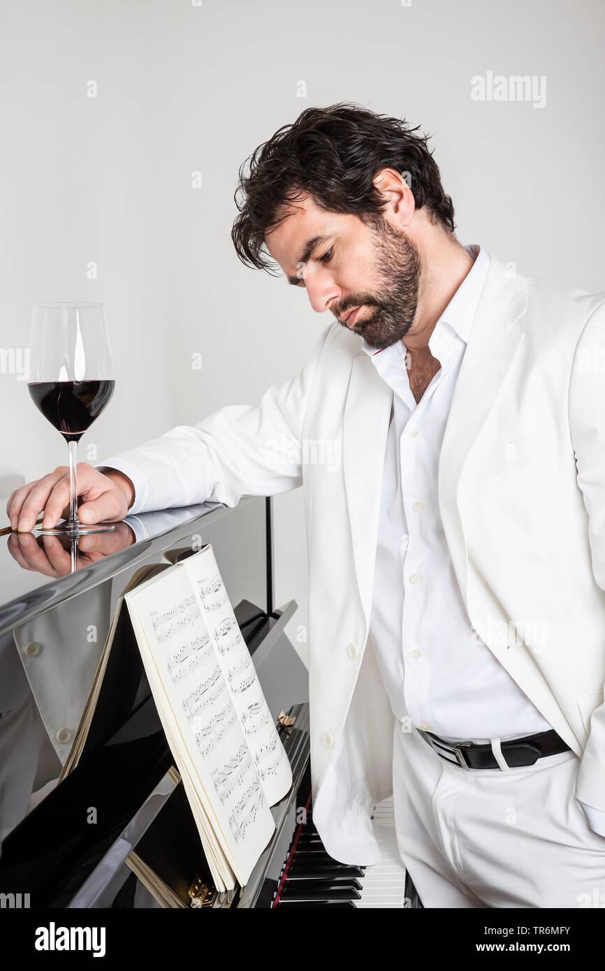 junger Mann im weissen Anzug steht nachdenklich am Klavier mit einem Glas Rotwein, Deutschland   young man in white suit standing at a piano, Germany - Stock Image