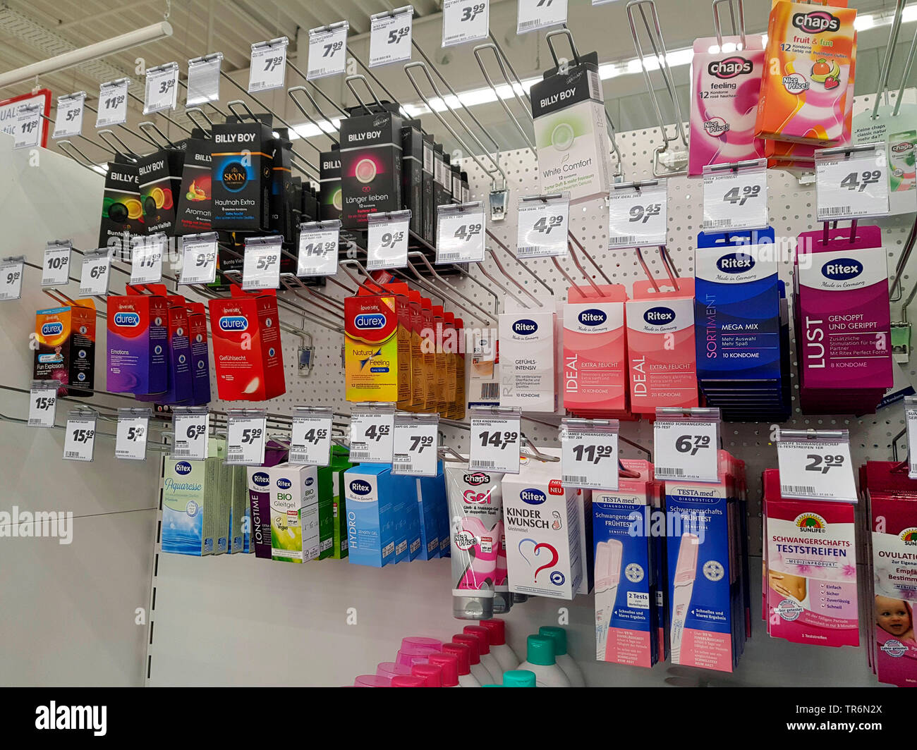 assortment of condoms, glide gel and pregnancy test in a supermarket, Germany - Stock Image