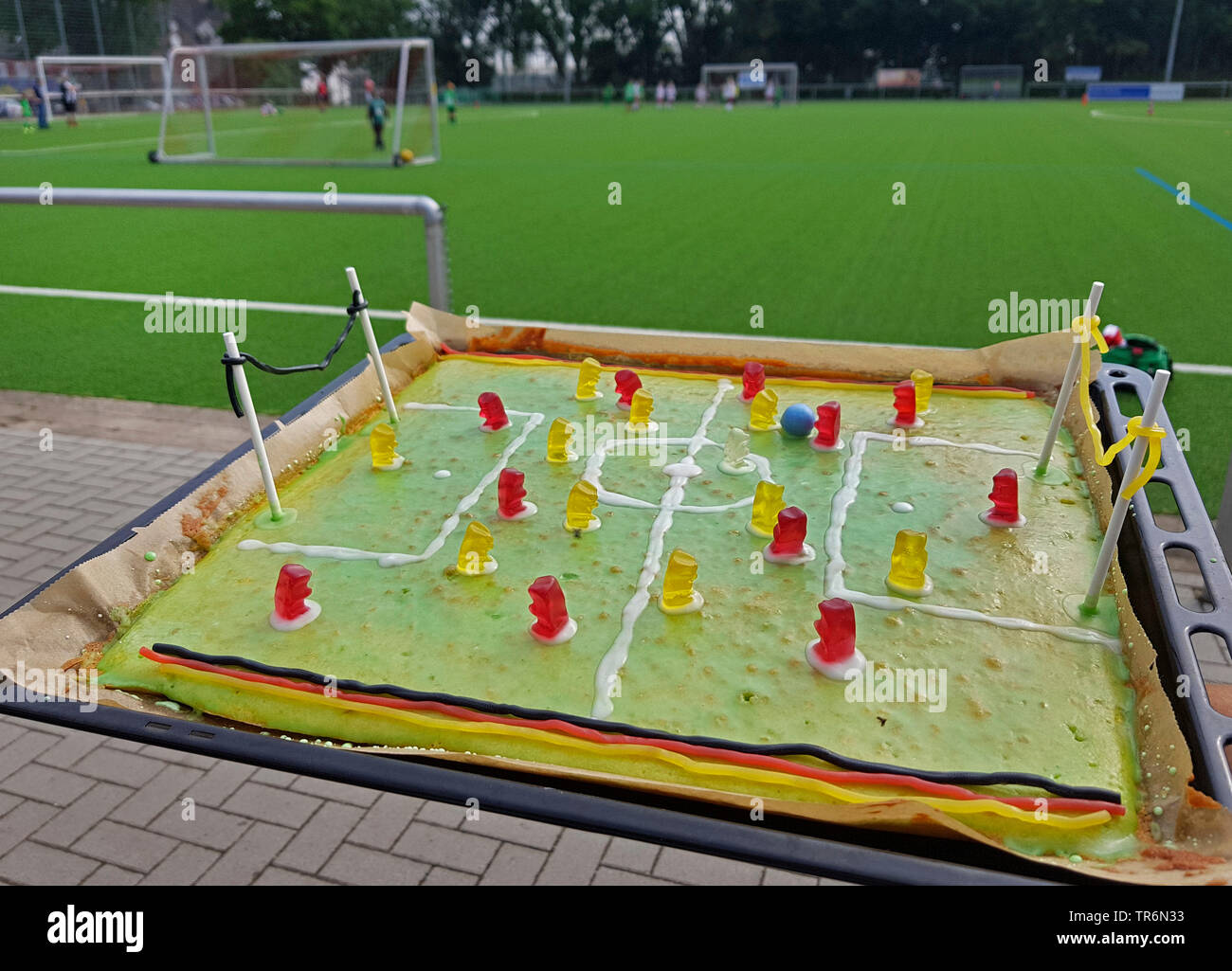 selbstgemachter Fussballkuchen mit Gummibaerchen auf einem Backblech am Rand eines Fussballplatzes | selfmade football cake at the border of a footbal - Stock Image