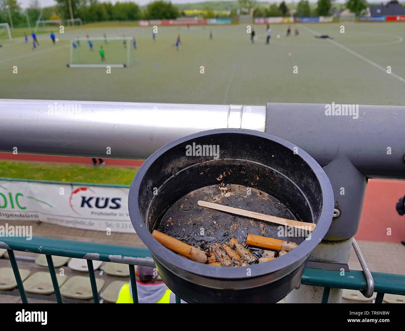 Aschenbecher mit Zigarettenkippen auf der Tribuene eines Sportplatzes, Deutschland   cigarette stubs in an ashtray at football stands, Germany   BLWS4 - Stock Image