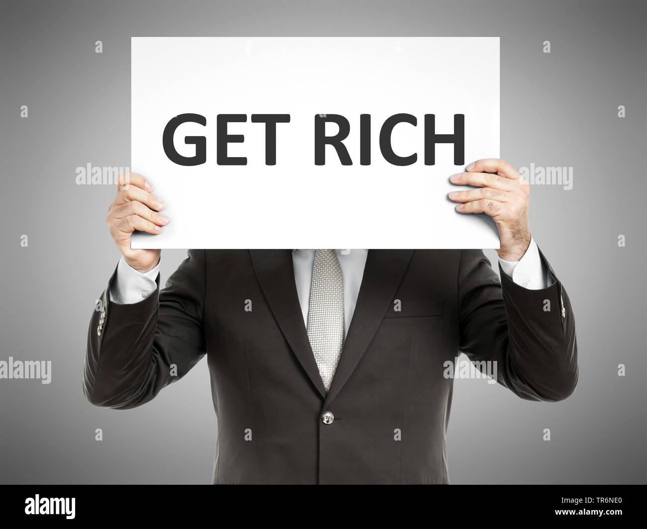 businessman holding a sign with the inscription Get Rich, Germany Stock Photo