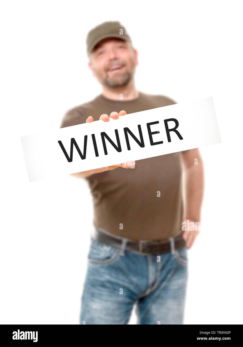 Mann haelt ein Schild in der Hand mit der Aufschrift Winner, Sieger, Deutschland | man with a sign in the hands with the inscription winner, Germany | - Stock Image