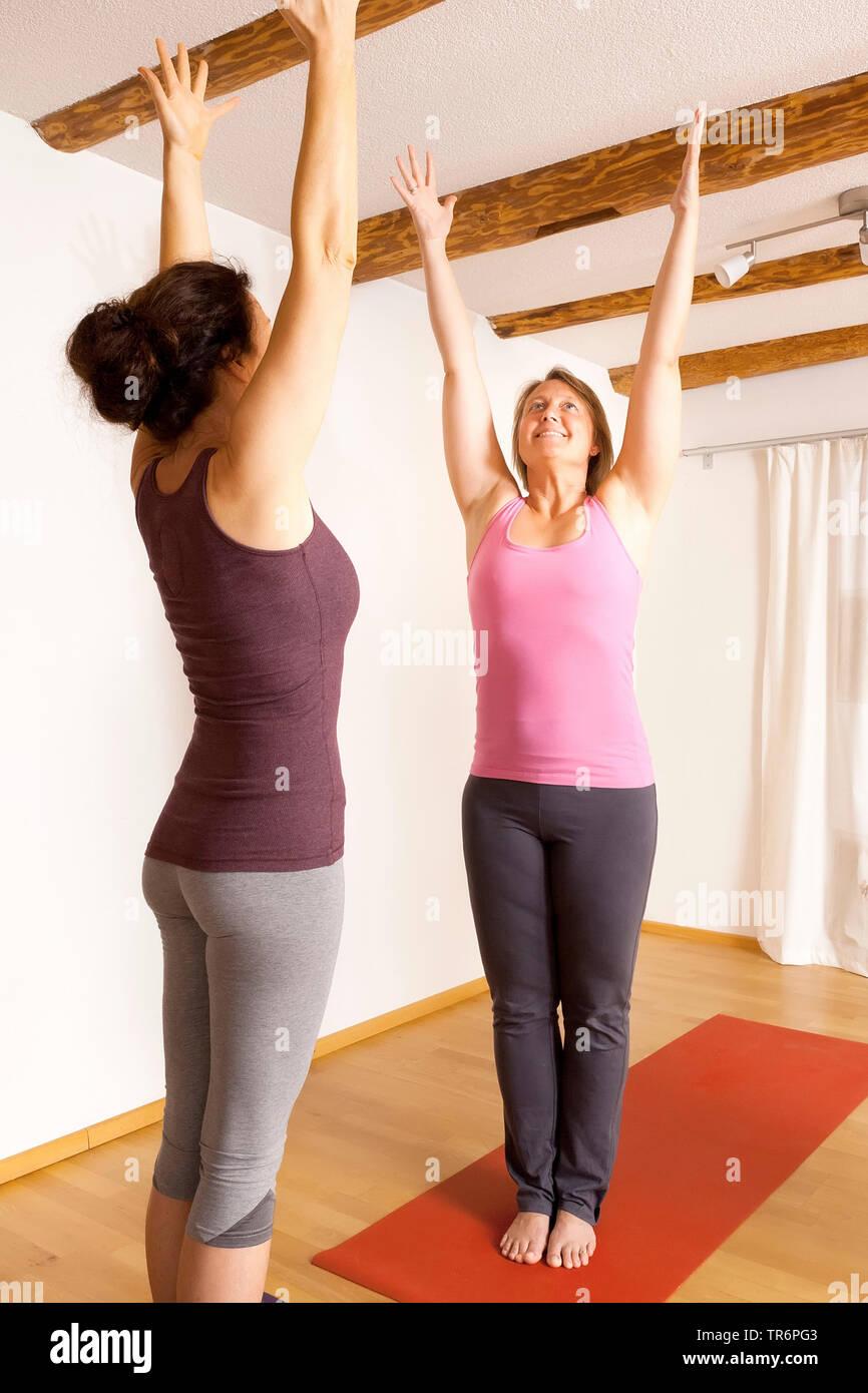 zwei junge Frauen machen Yogauebungen im Wohnzimmer, strecken sich | two women doing yoga in the living room at home | BLWS488766.jpg [ (c) blickwinke - Stock Image