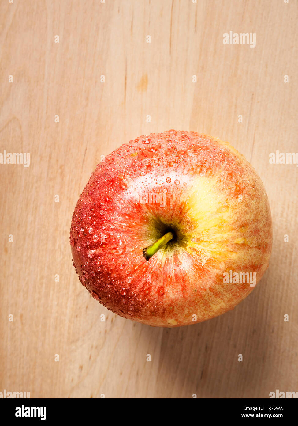 apple (Malus domestica), red apple on a woode plate Stock Photo