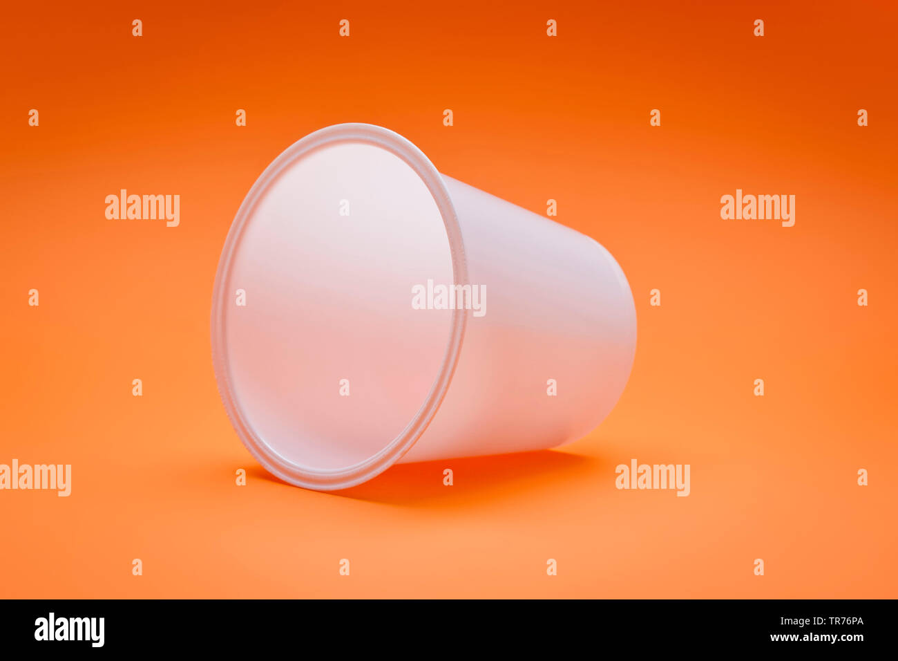 weisser Plastikbecher auf orangefarbenem Untergrund | white empty plastic cup on an orange background | BLWS499556.jpg [ (c) blickwinkel/McPHOTO/M. Ga - Stock Image