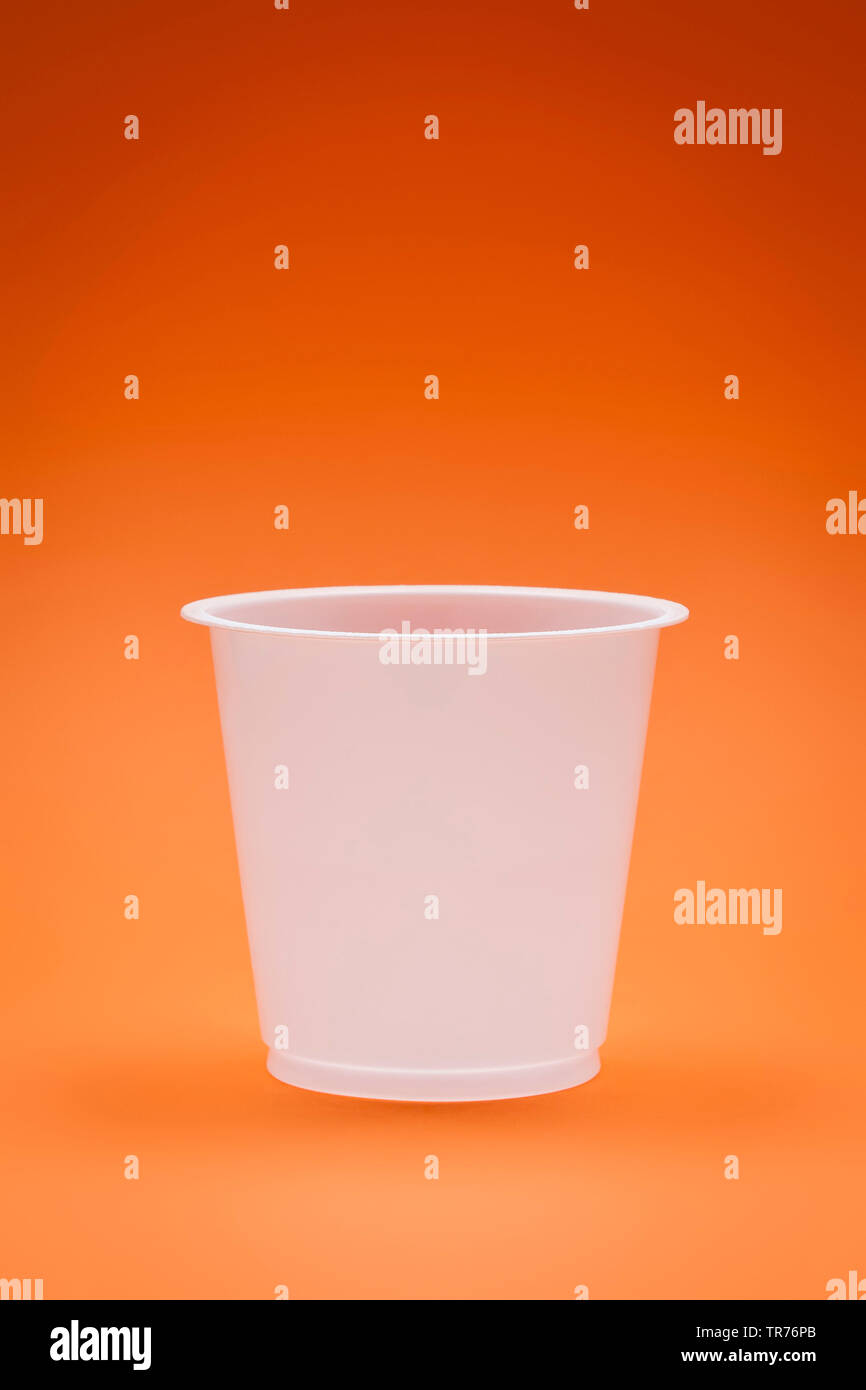 weisser Plastikbecher auf orangefarbenem Untergrund | white empty plastic cup on an orange background | BLWS499557.jpg [ (c) blickwinkel/McPHOTO/M. Ga - Stock Image