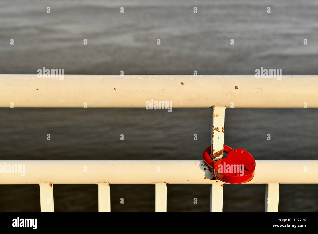 The white painted railing of the embankment of the river. With a red lock mounted on a metal pipe. Lattice lines on the background of water. On the Su - Stock Image