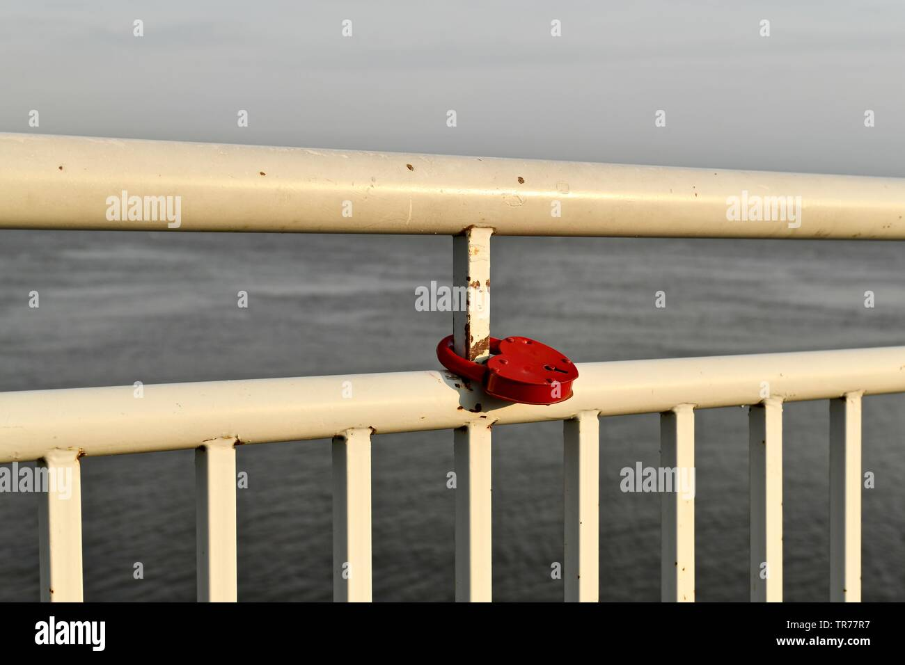 A red metal lock, in the shape of a heart, hangs on the slightly rusty white railing of the river embankment. A railing of a metal pipe divides the ba - Stock Image