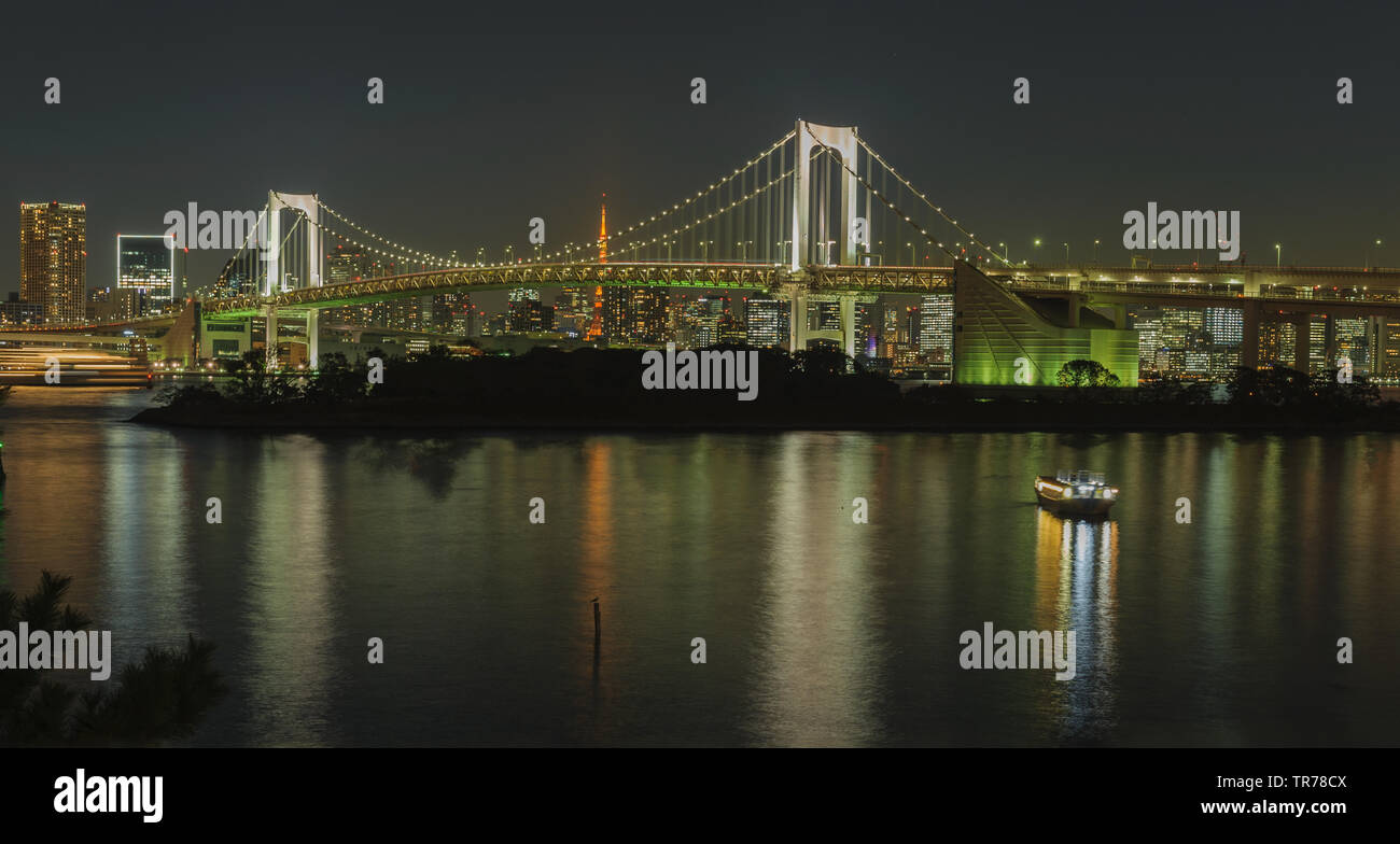 Iconic view from Odaiba on Reinbow Bridge and Tokyo Tower in illuminated City centre of japans capital at evening, October 2018 Stock Photo