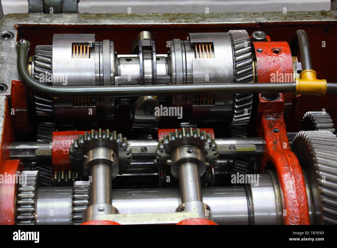 Under the bonnet of a Henry Milnes 13 inch swing gap bed lathe showing the clutch assembly unit with direction selector and general picture of gears. - Stock Image