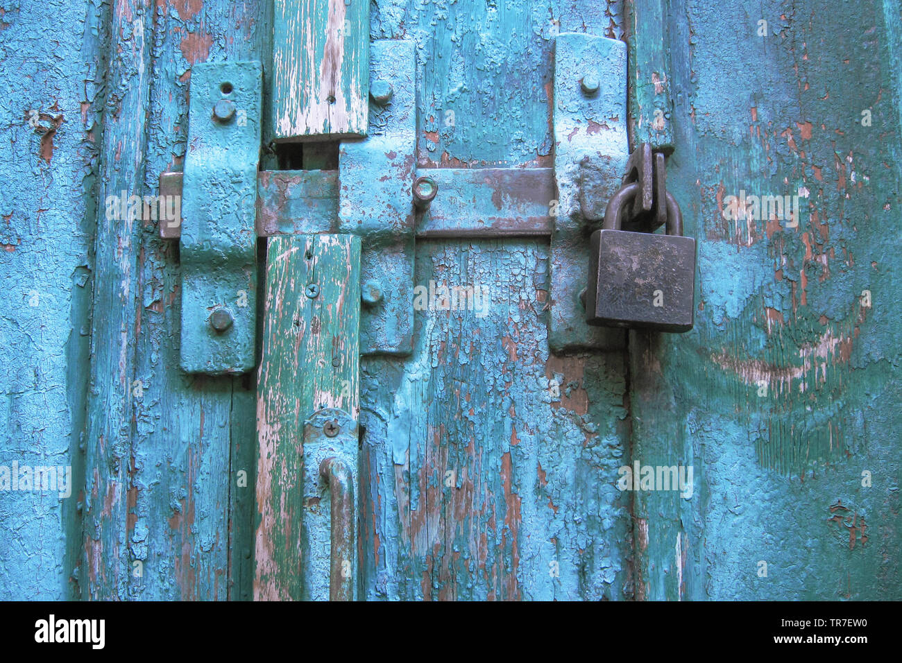 Vintage latch and closed padlock on weathered scratched wooden door. Concept of security and privacy protection. Textured grunge background Stock Photo