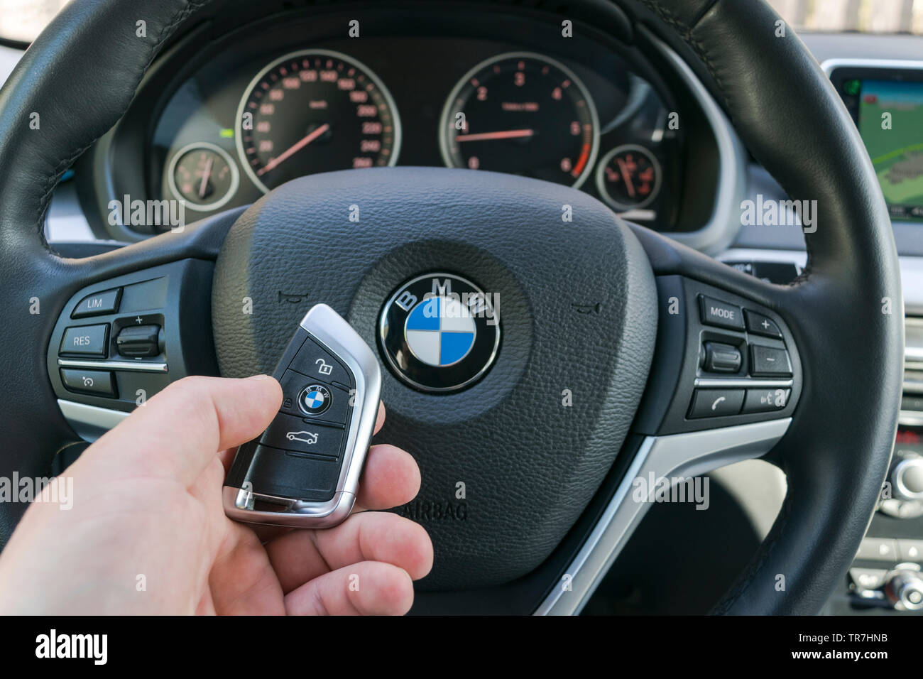 Sankt-Petersburg Russia, April 4, 2018: Man's hand holding a wireless BMW X5 F15 car key in black leather car interior. Modern Car interior details. C - Stock Image