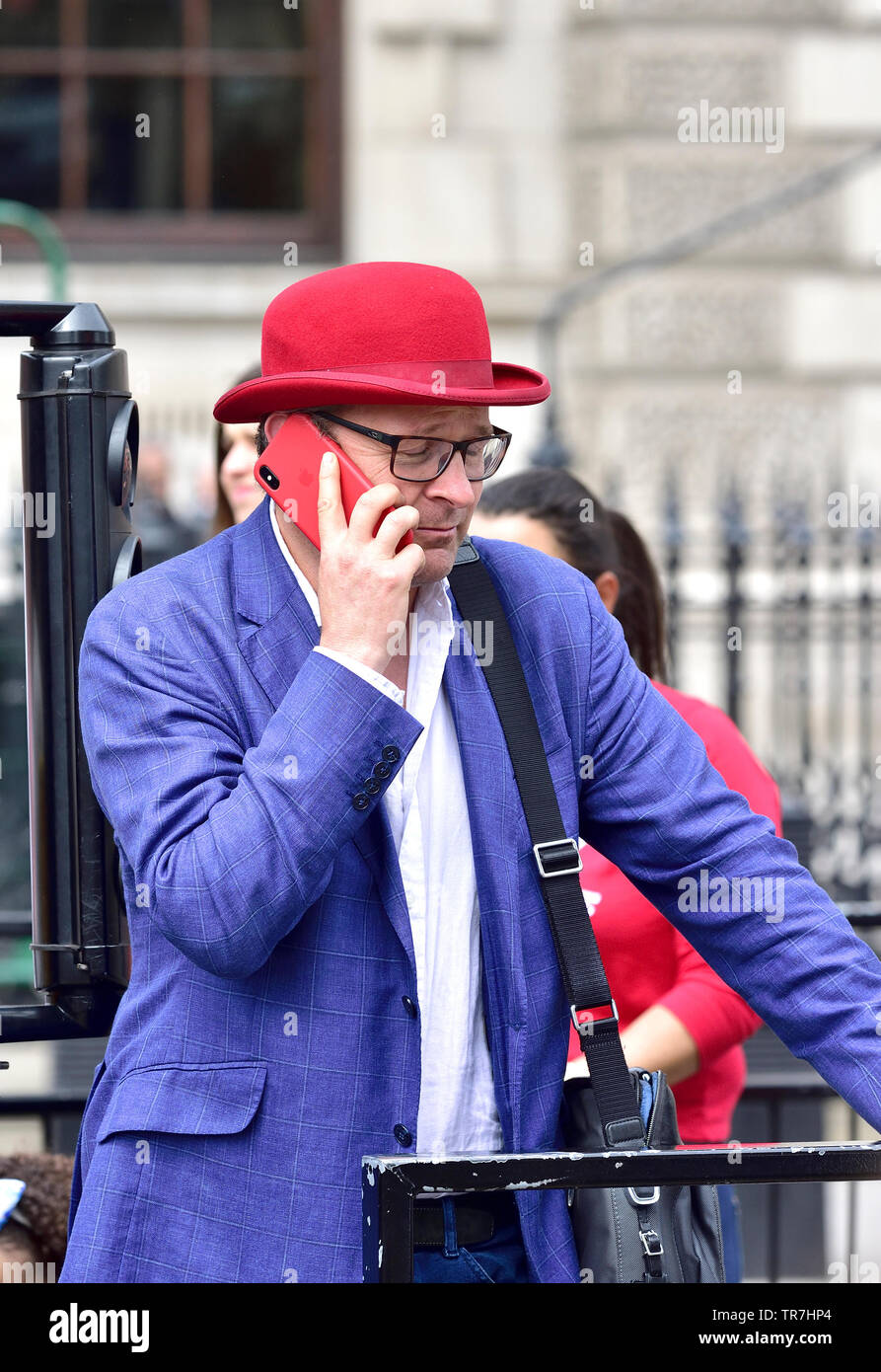 London, England, UK. Man in a red bowler hat using a red mobile phone in Whitehall - Stock Image