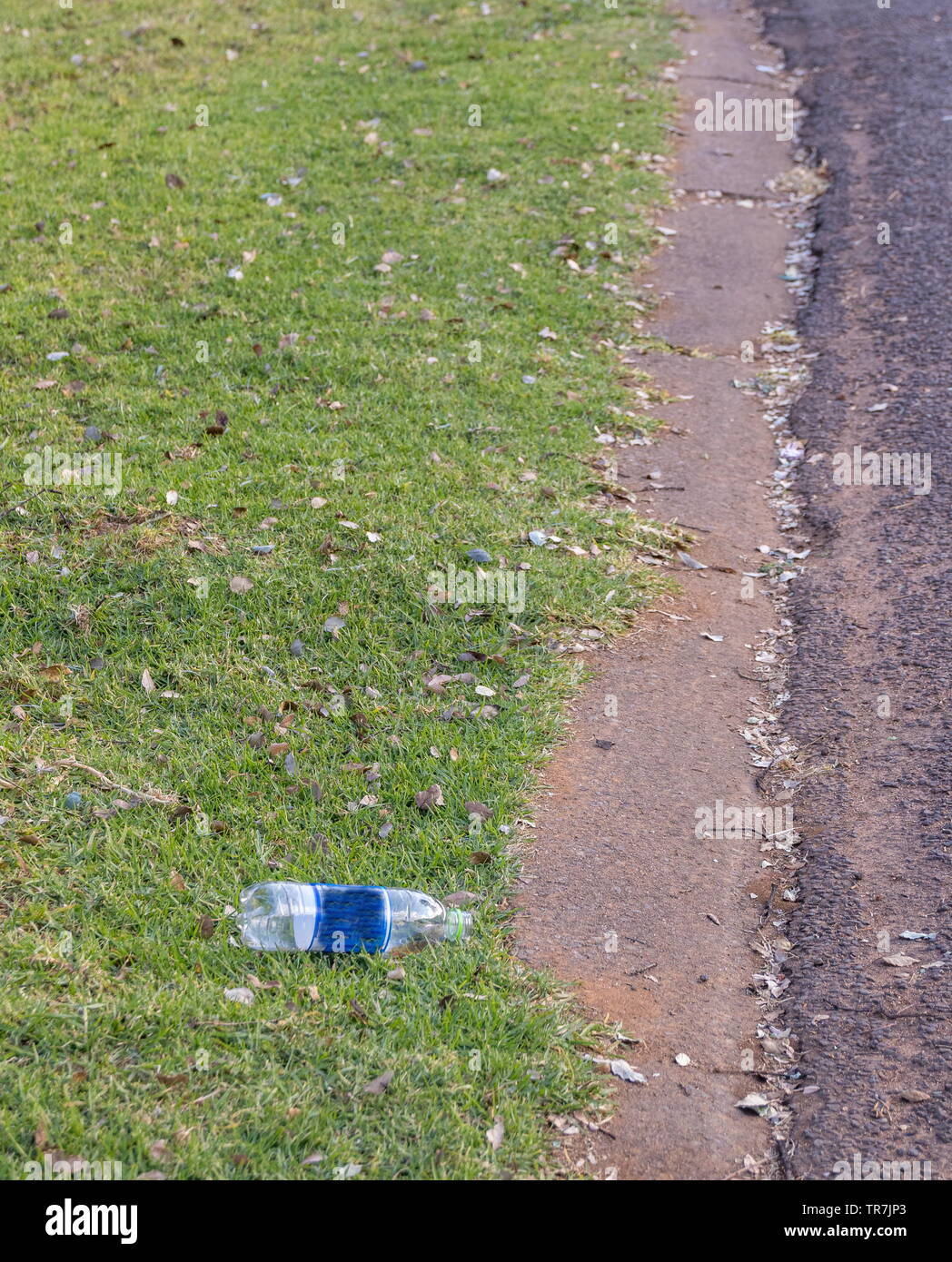 A plastic bottle lies discarded on a pavement next to a public street image with copy space - Stock Image