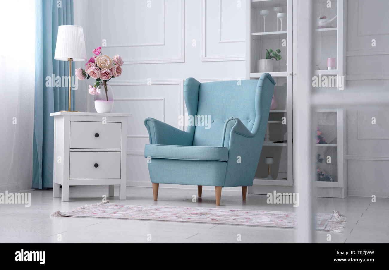 Blue classic armchair with table lamp and flower vase Stock Photo