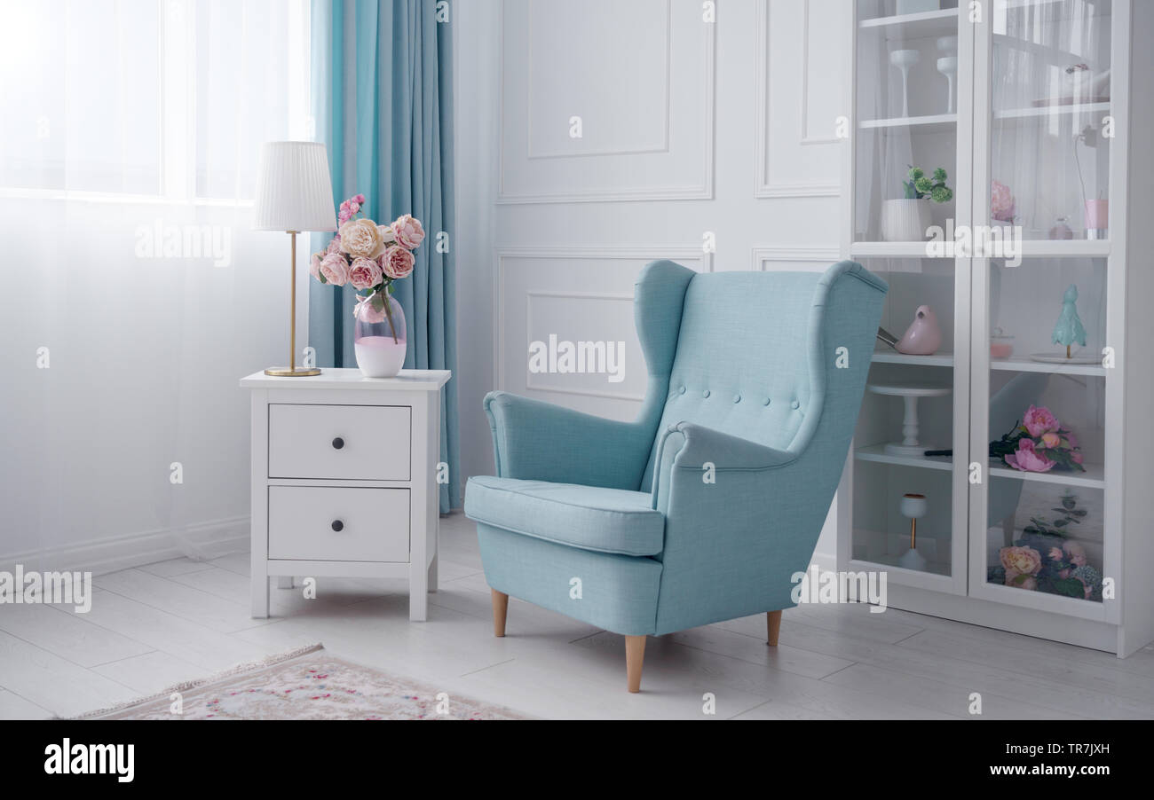Blue classic armchair and bedside table with table lamp and flowers vase in white room Stock Photo