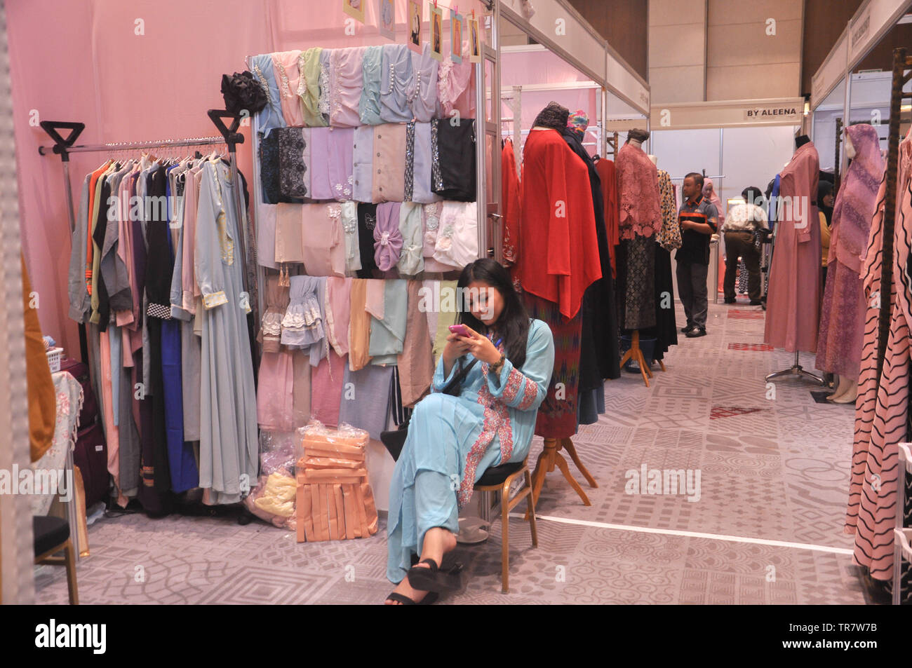 A booth keeper checks her phone at Indonesia Moslem Fashion