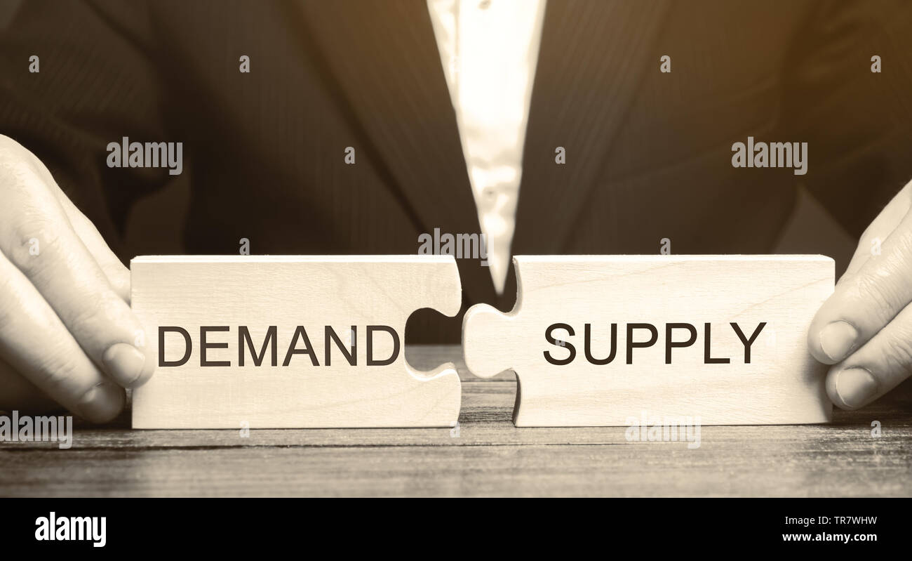Businessman collects wooden puzzles with the word Demand and Supply. The concept of the labor market. Economic theory, relationships. Business and com - Stock Image