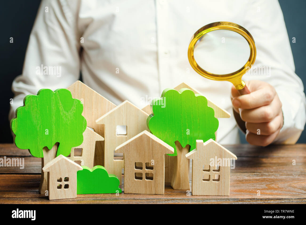 A man holds a magnifying glass over wooden houses and trees. Real estate valuation and selection of a place for the construction of new buildings. Eva Stock Photo