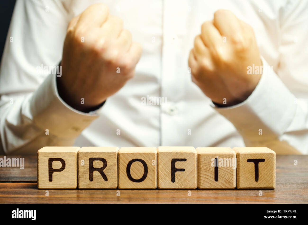 Wooden blocks with the word Profit and businessman. Favorable successful business. Profitable contract. The concept of obtaining material or moral ben - Stock Image