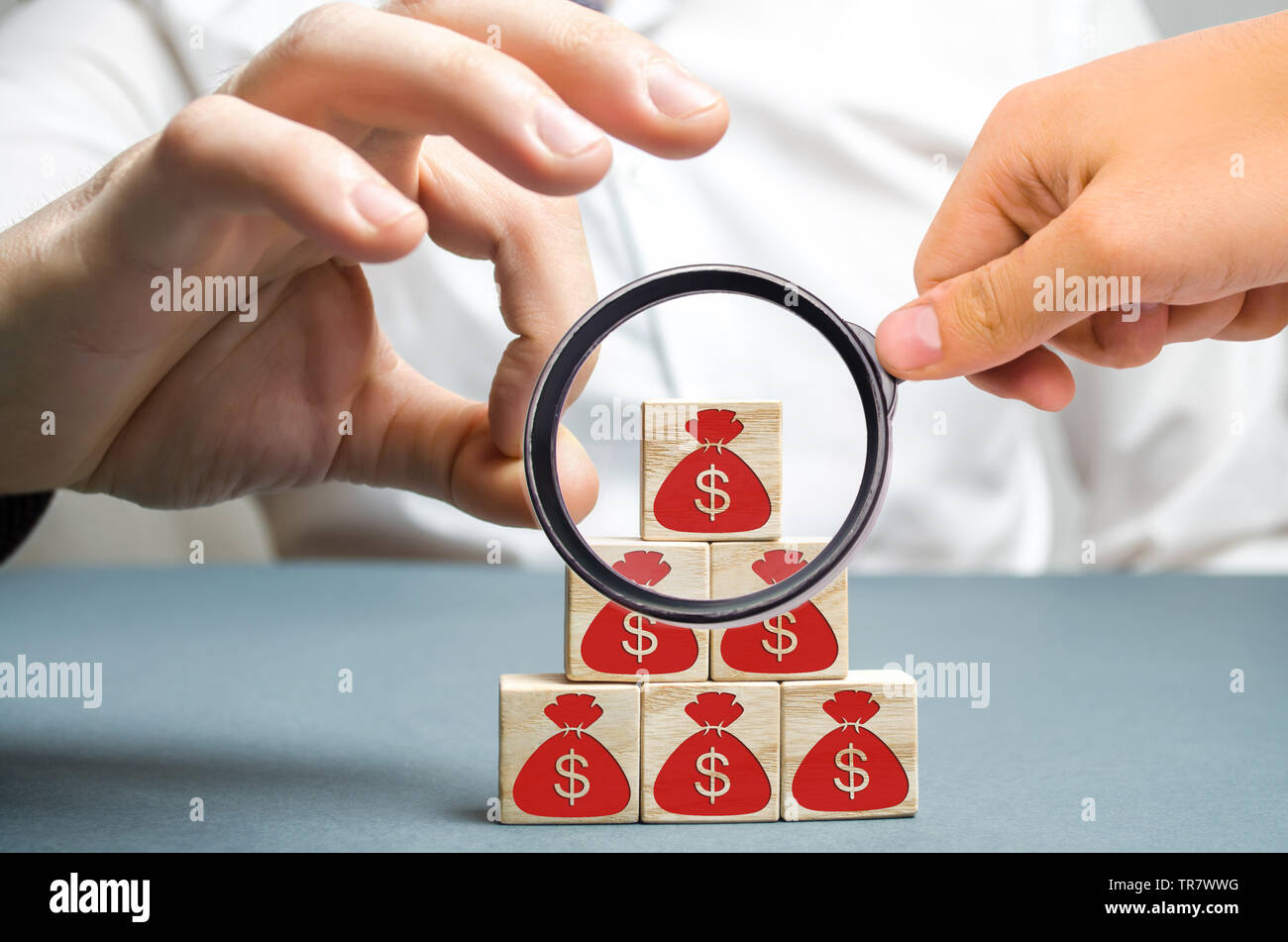 Businessman removes a cube with a picture of dollars. Bankruptcy concept. Economic recession. Financial crisis. Capital outflow. Sabotage of the econo - Stock Image