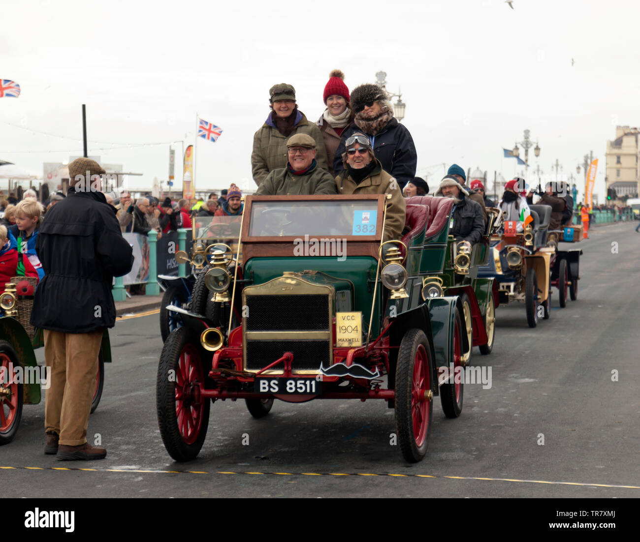 Mr Andrew Bailey and his passengers celebrate  after finishing the 2018 London to Brighton Veteran Car Run in a 1904 Maxwell - Stock Image