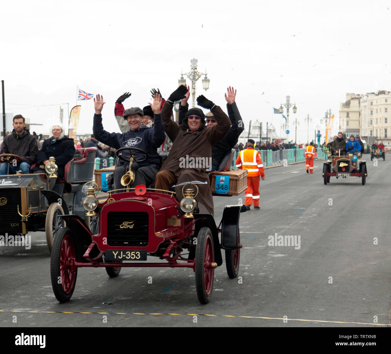 Mr Rick Lindner and his passengers celebrating, after they completed the 2018 London to Brighton Veteran Car Run, in  a 1904 Ford. Stock Photo