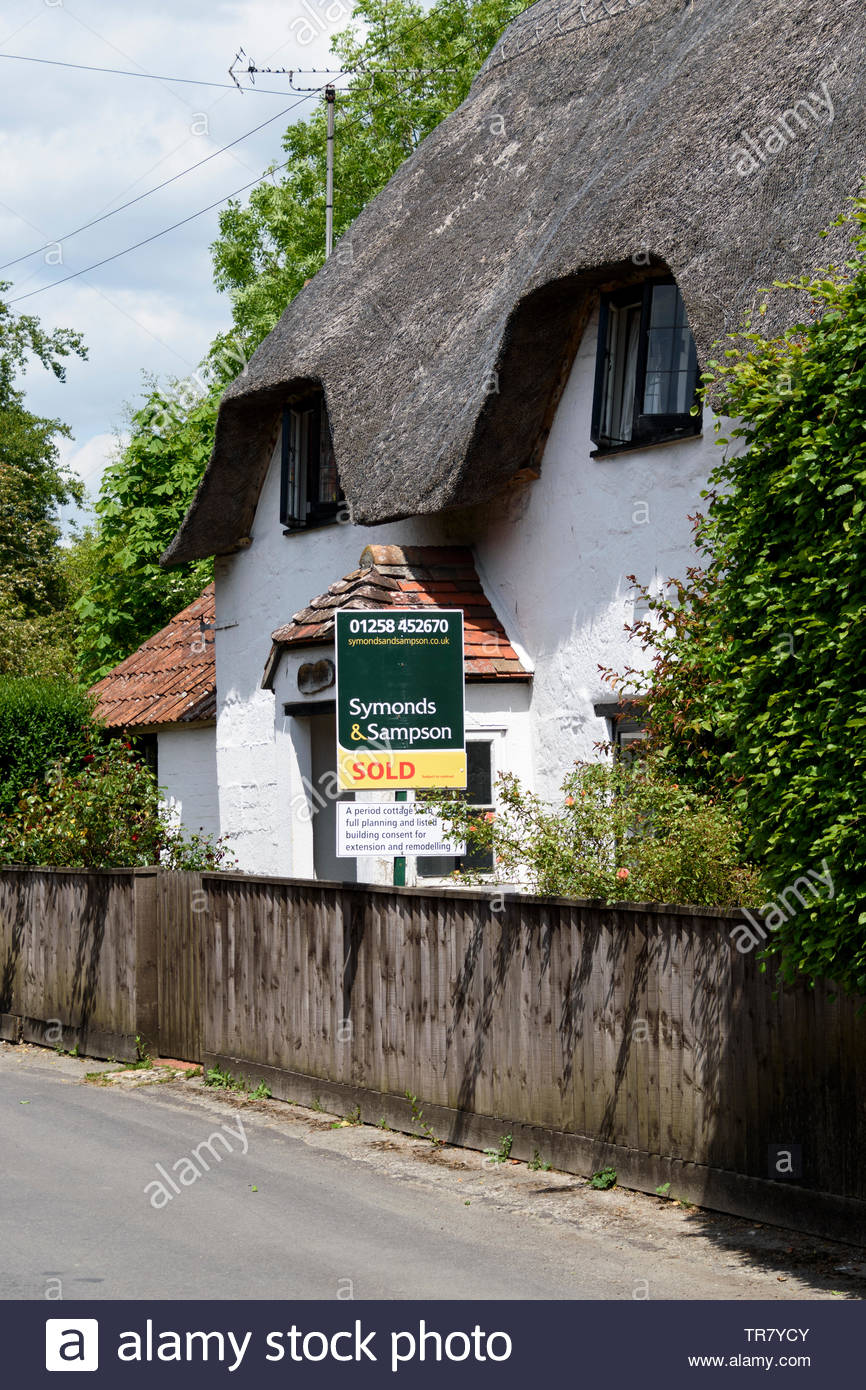 Picturesque view of a rural thathed cottage with a Symonds & Sampson Sold board outside, Dorset, England, UK Stock Photo