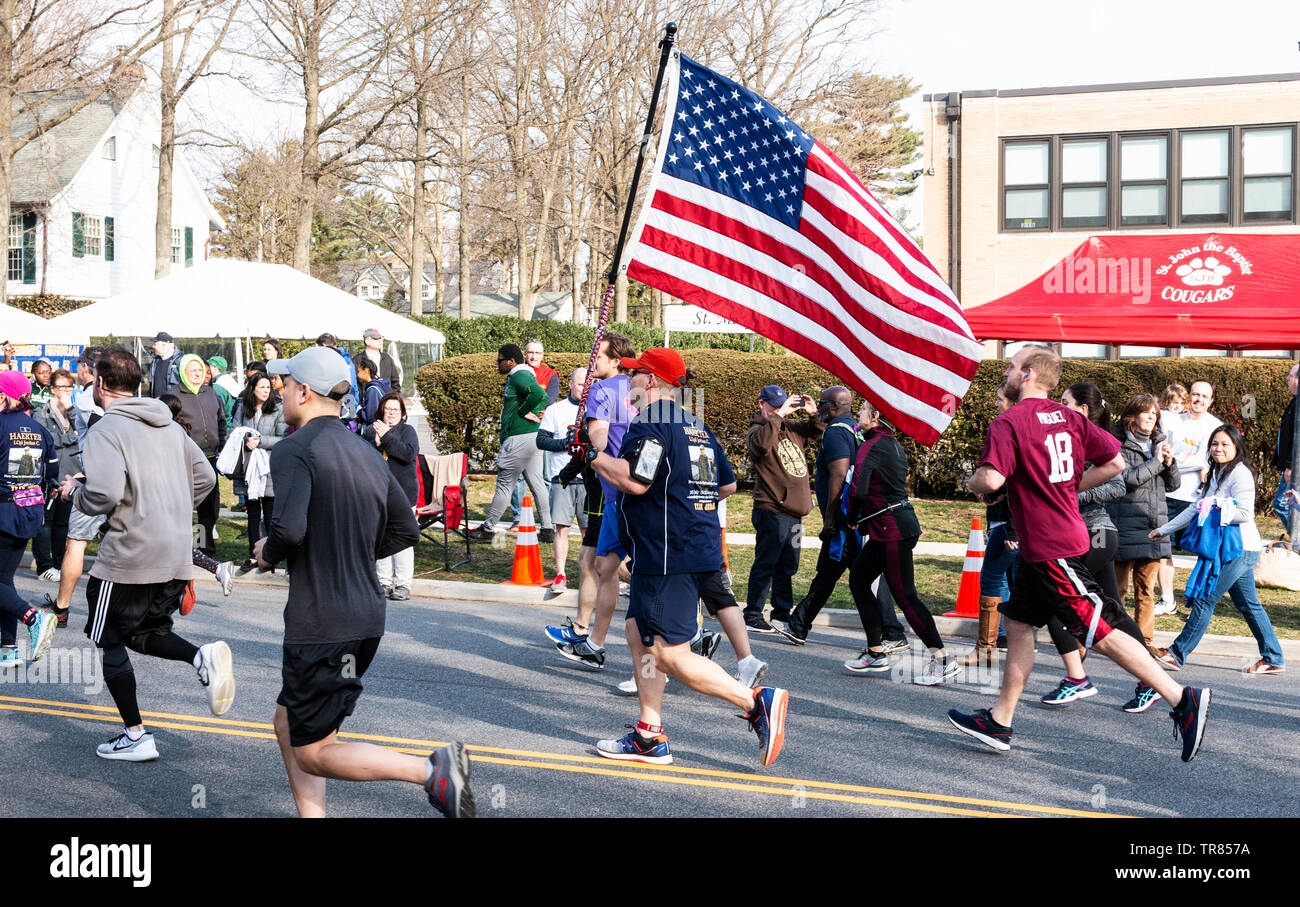 Garden City, New York, USA - 30 March 2019: A runner is carrying an American flag during a 5K charity road race. - Stock Image