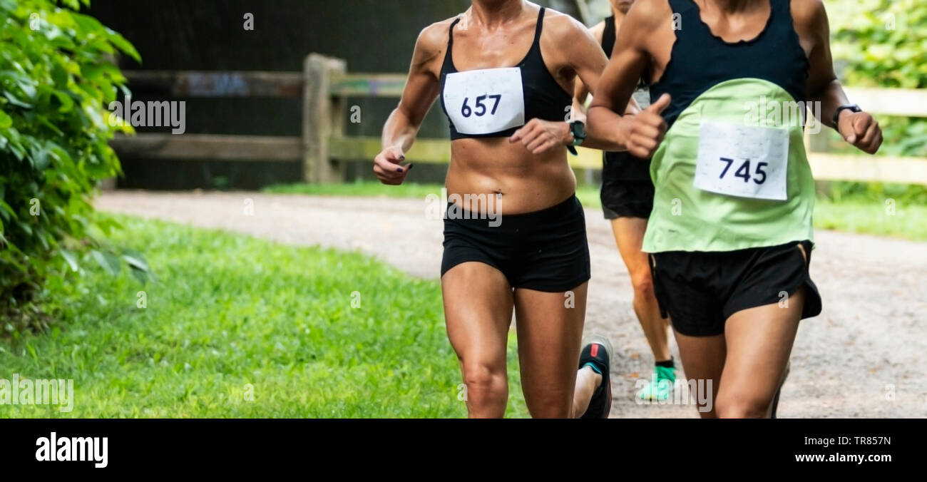 Three competitiors racing a 5K race after coming out of a tunnell on a dirt path with as little clothing on as possible due to extreme heat. - Stock Image