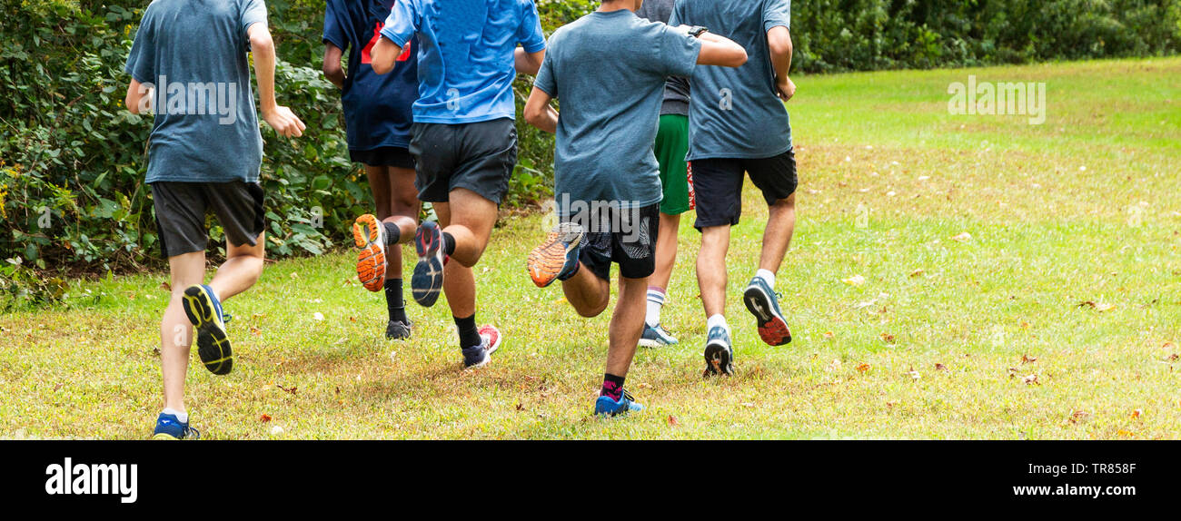 A high school boys cross country team is running together on a grass path in a local park during practice. - Stock Image