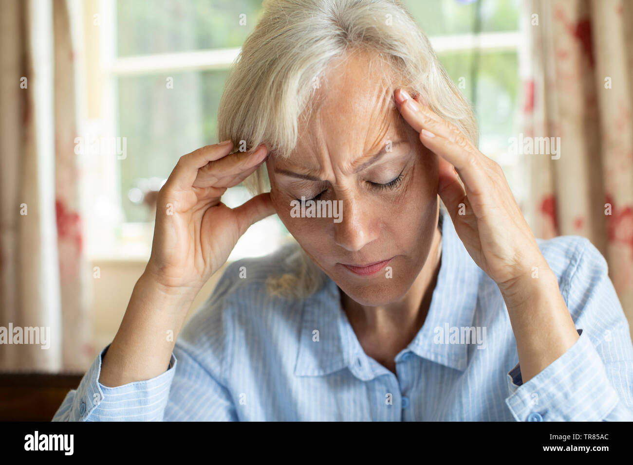 Senior Woman At Home Suffering With Migraine Headache - Stock Image