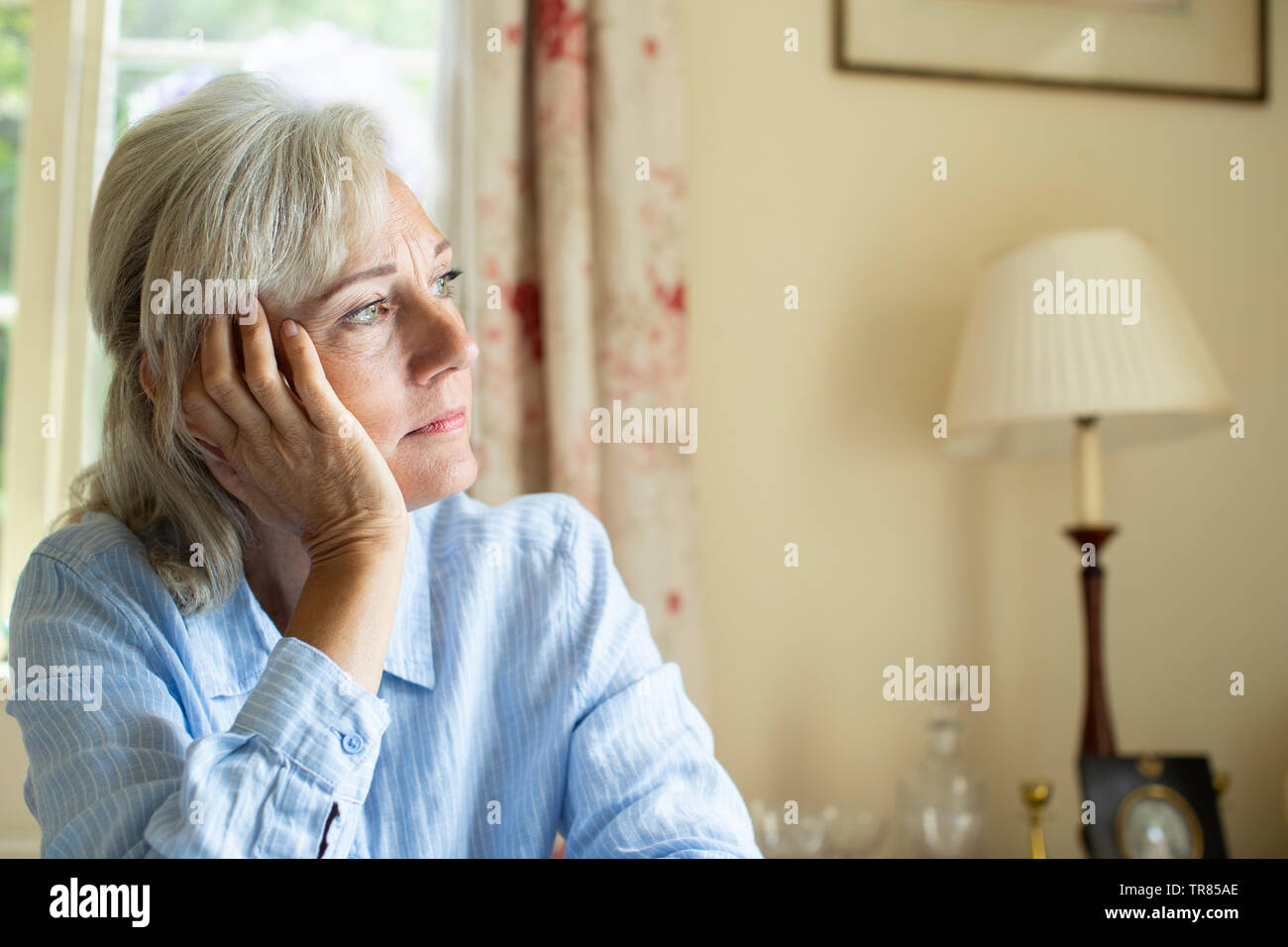 Senior Woman Suffering With Depression Looking Out Of Window At Home - Stock Image