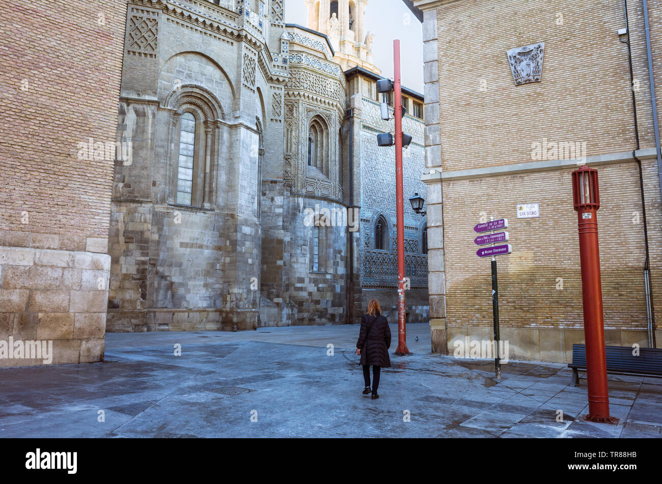 Zaragoza, Aragon, Spain : A woman walks past the north side of La Seo Cathedral of the Savior, with romanesque, mudejar and gothic parts. It was built - Stock Image