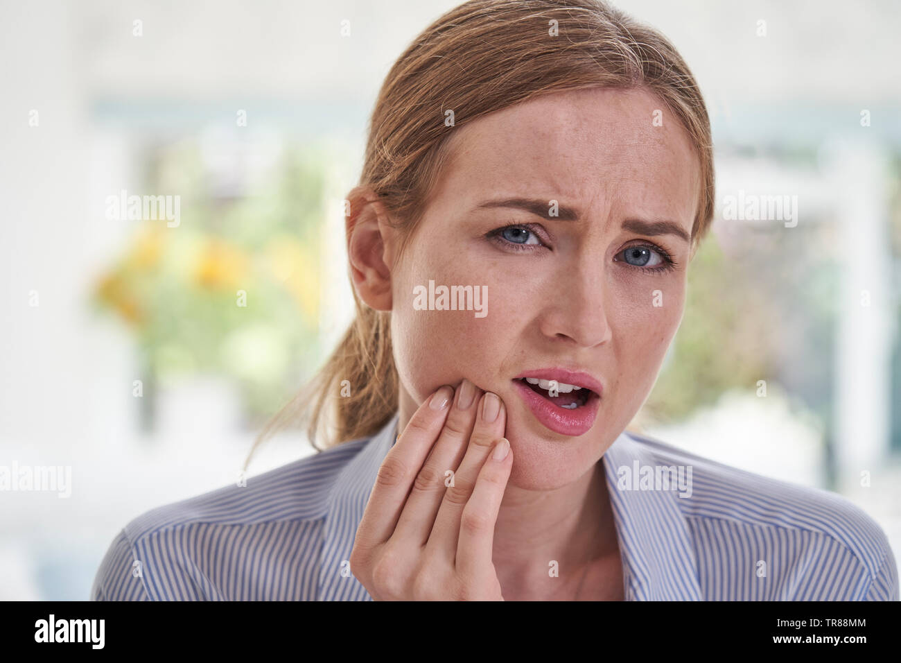 Portrait Of Young Woman Suffering With Toothache Touching Jaw - Stock Image