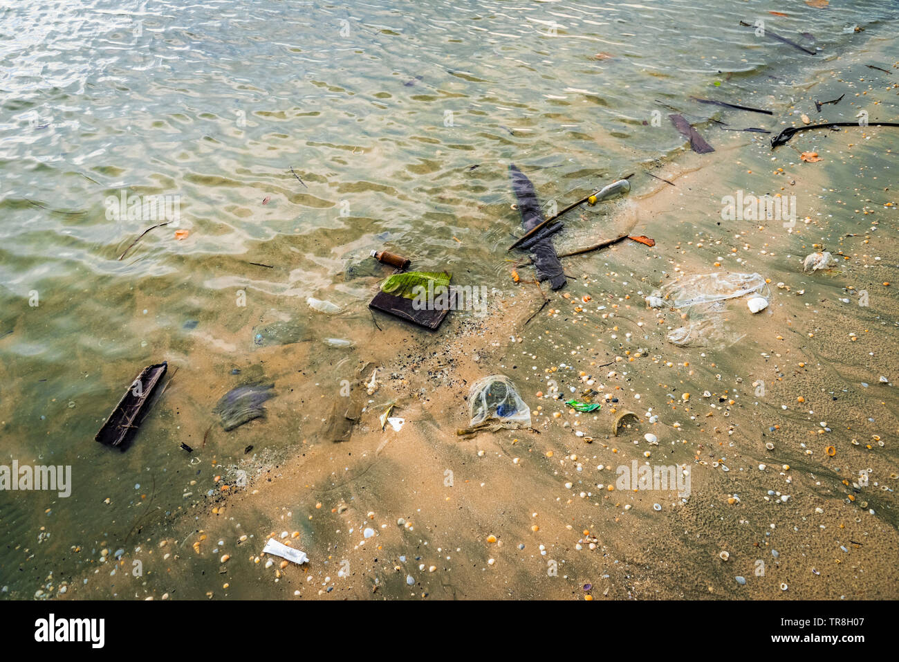 garbage on beach stop plastic pollution save the earth concept / sea water pollution with trash on sand - Stock Image