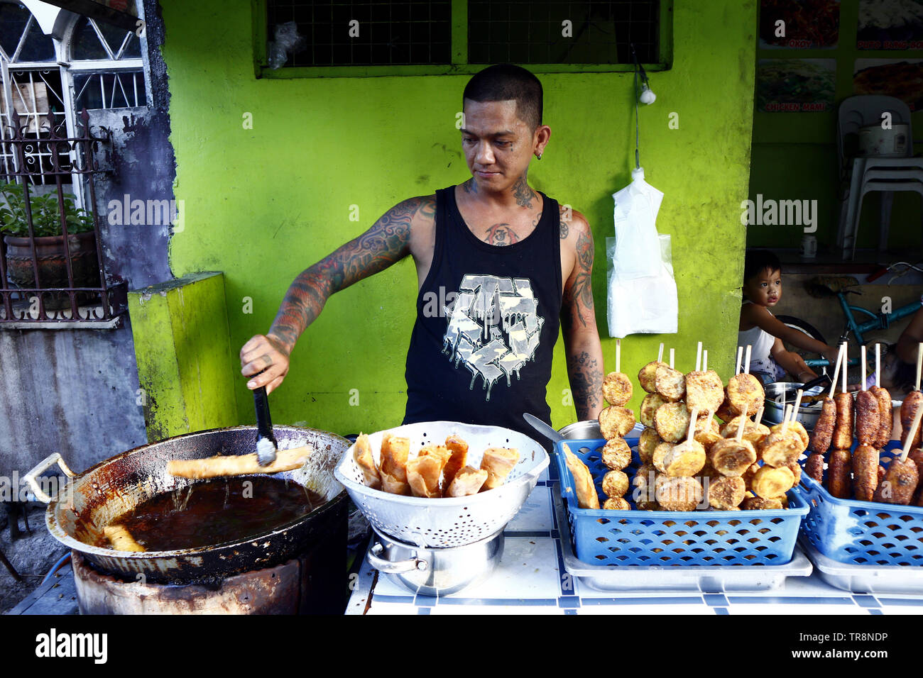 ANTIPOLO CITY, PHILIPPINES – MAY 30, 2019: A street vendor cooks assorted sweet snack items in his makeshift store on a sidewalk along a street. - Stock Image