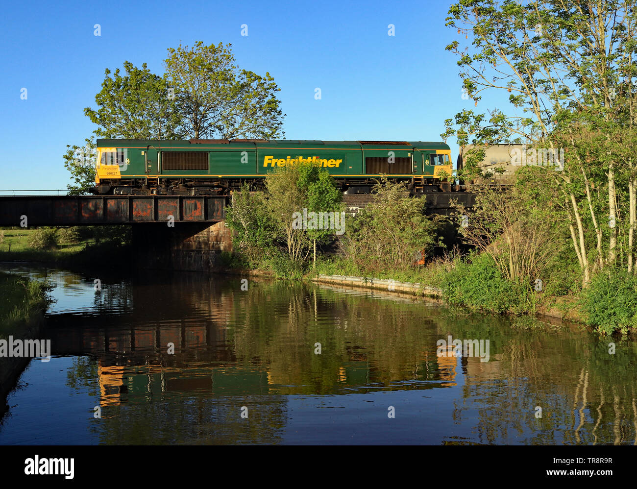 Green Freightliner diesel locomotive 66621is reflected in the water as it crosses the Trent and Mersey canal travelling along the Middlewich line. - Stock Image