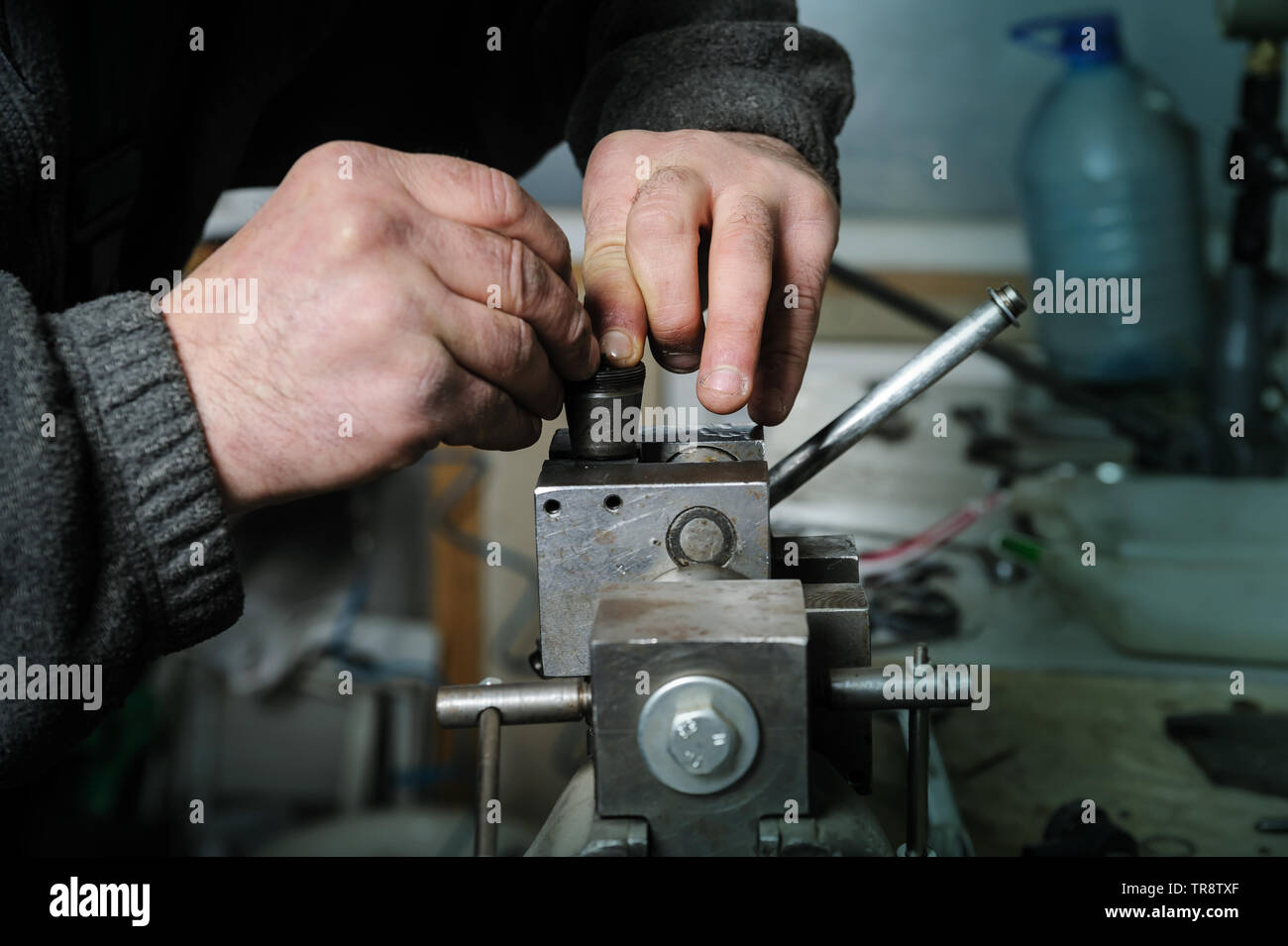 Mechanics repairing a diesel injector. Mans hands disassemble a injector pinched in a vise. - Stock Image