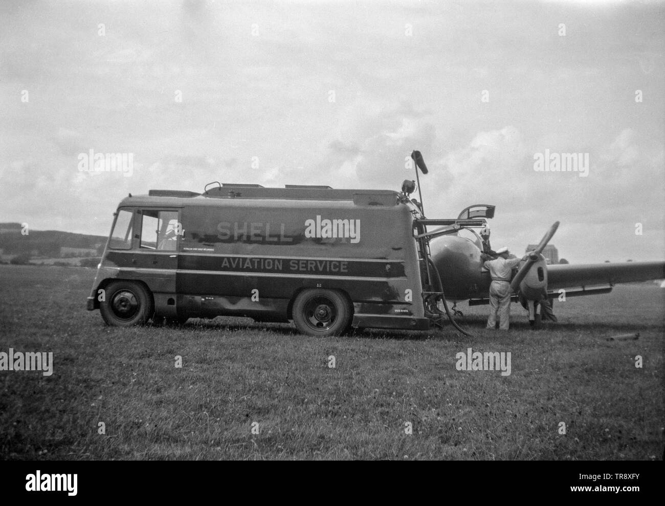 A Miles Gemini Twin Engined British Light aircraft, being refilled from an aviation fuel tanker belonging to Shell Aviation. Vintage black and white photograph taken in the 1950s. - Stock Image