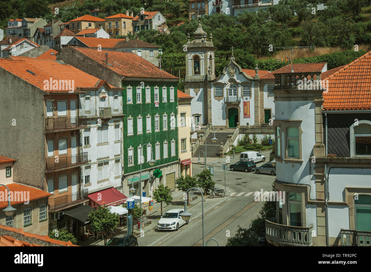 Street with colorful buildings and baroque church in a hilly landscape at Seia. A nice village of Portugal also known for its delicious cheese. - Stock Image