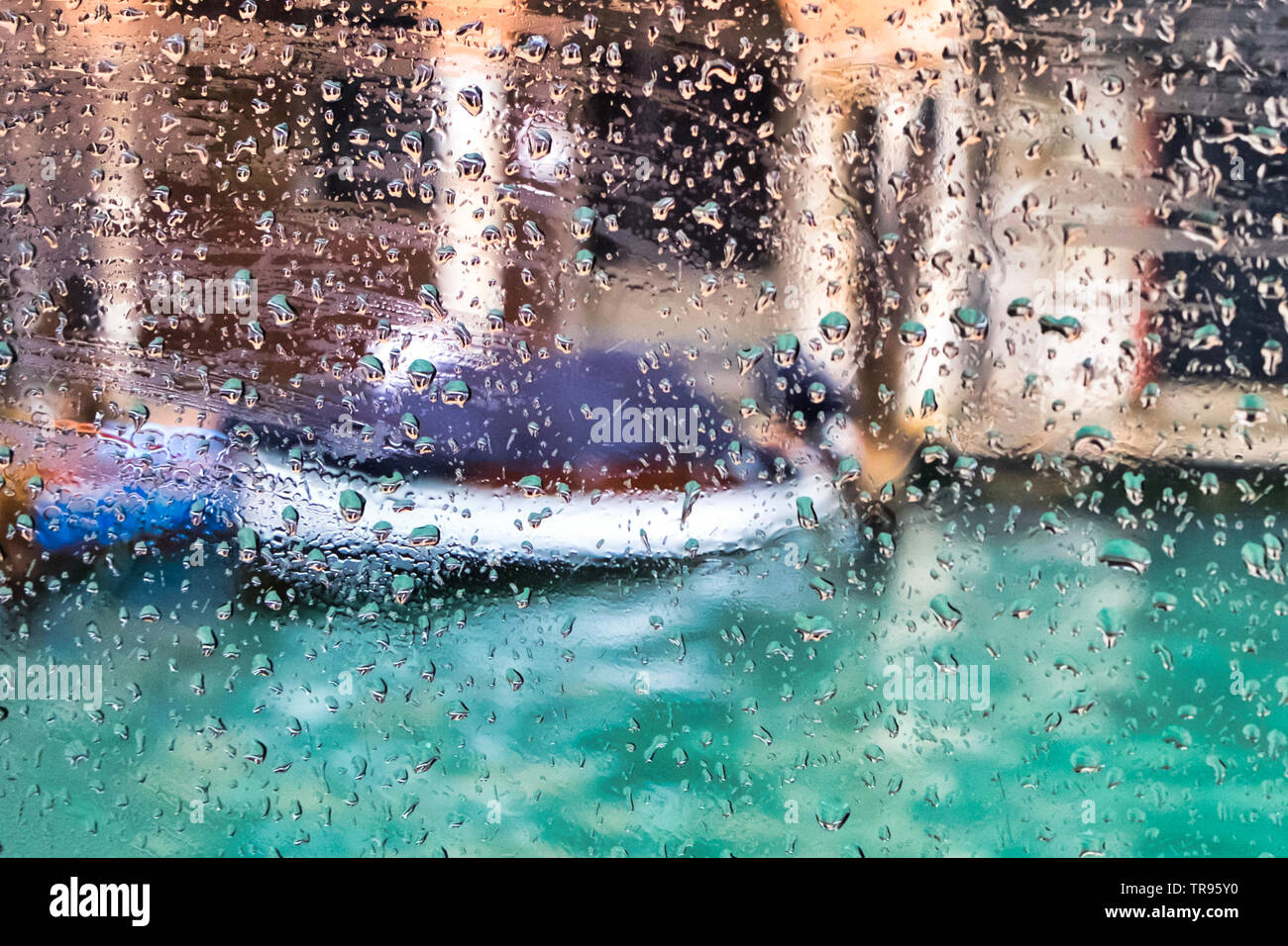 Traditional gondola boat, old Venetian palazzo and blue canal in Venice, Italy through the blurred window with rain drops - Stock Image